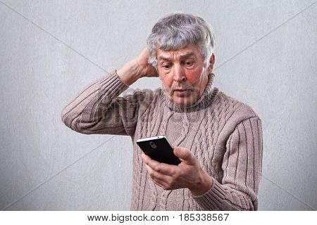 A Shocked Mature Man Holding Mobile Phone Touching His Head With A Hand. An Elderly Person With Gray
