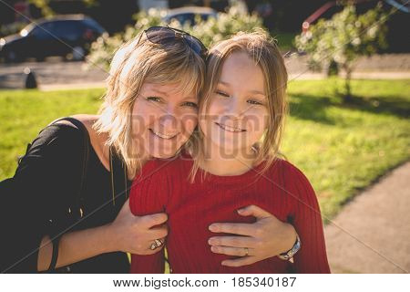 Beautiful mother and daughter posing at the park in spring day