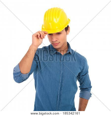 young construction engineer holding his safety helmet and looks down on white background