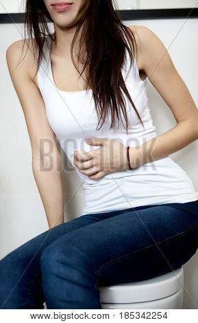 Woman sitting on toilet bowl, heaving belly ache