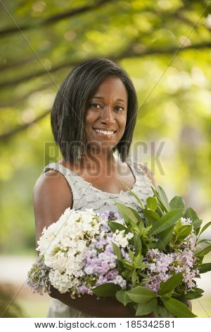 Smiling African American woman holding bouquet of flowers
