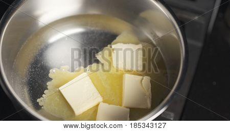 Handheld shot of shot of butter melting in water, 4k photo