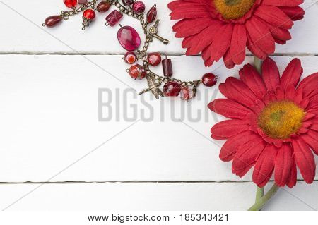 Red chrysanthemum / daisy flowers on white wooden background close up with red glass and gold charm bracelet - space for text