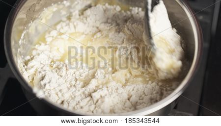 Handheld shot of mixing flour with butter mix for making choux dough, 4k photo