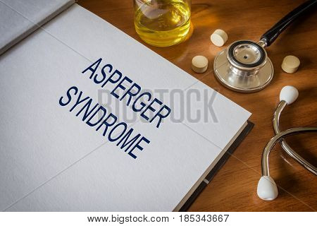 Asperger syndrome written on book with tablets. Medicine concept.