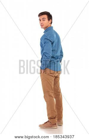 full body picture of a casual man looking back over his shoulder on white background, back view