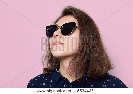 Fashion and style concept. A stylish elegant young brunette wearing sunglasses looking up isolated over rose-coloured background. Portrait of attractive young model wearing sunglasses