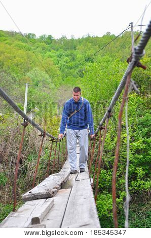 Man walking on a rotten old suspension bridge. Men crossing the river to the old damaged bridge