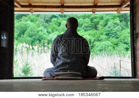 Buddhist Meditation. Older man meditating in a wooden house. Senior man practicing meditation and looking the nature