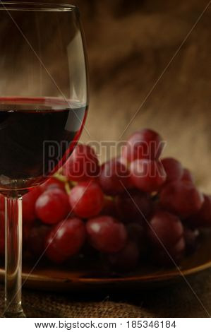 Image of red wine close-up with grape in background