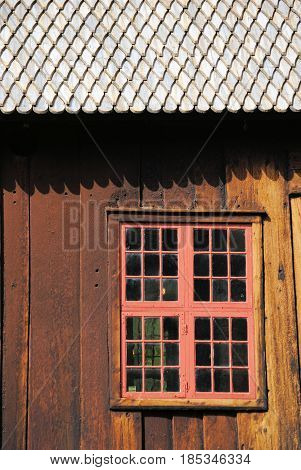 Window of old wooden church in Norway