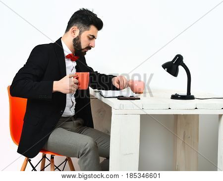 Bearded man short beard. Caucasian serious hipster with moustache holding orange mug looking to mobile phone at white wooden table wearing black jacket white shirt red bow tie isolated on white