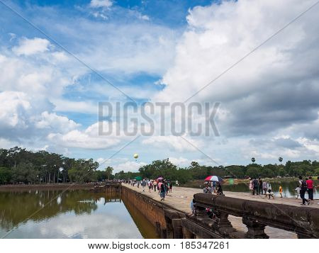 Siem Reap Cambodia - October 30 2016: Tourists walking back along the stone bridge after visiting Angkor Wat UNESCO World Heritage site in Cambodia