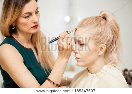 Makeup trainer with a brush applying blush with a brush on model. Applying make up to a young beautiful model