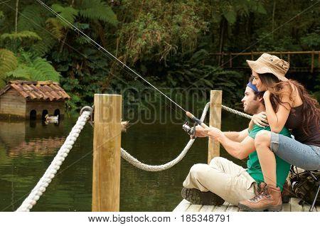 Hispanic couple fishing off pier