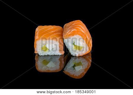 Rolls with daikon salmon and cream cheese on a black background with reflection