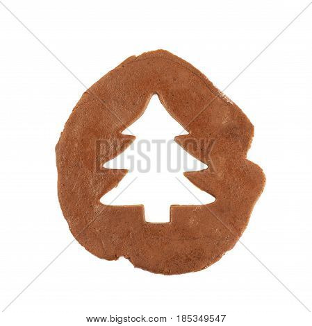 Rolled up thin layer of cookie dough and a christmas tree shaped cookie cut out of it, composition isolated over the white background