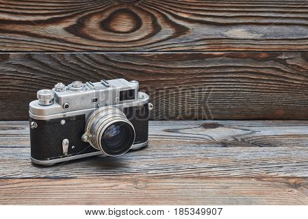 Vintage old retro 35mm rangefinder camera on wooden background with copy space