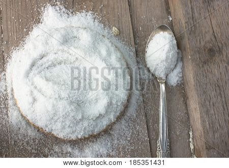 Common salt with silver spoon in a straw round bowl. top view. copy spase