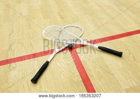 squash rackets and ball on the court near red line. Racquetball equipment. Photo with selective focus