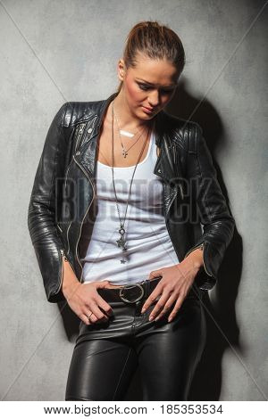 sexy blonde woman in leather clothes looking down while posing in studio