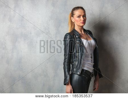 side view of a fashion woman in leather clothes posing in studio