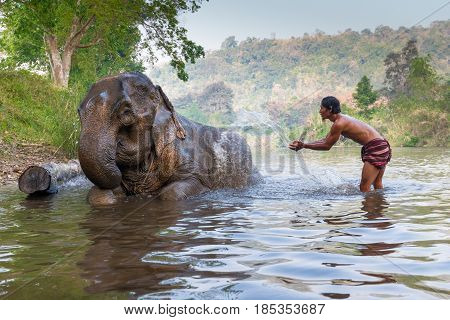 KANJANABURI, THAILAND-JANUARY 30 : An unidentified man shows playing with an elephant in a river in Sangkhlaburi, Kanjanaburi, Thailand on January 30, 2015