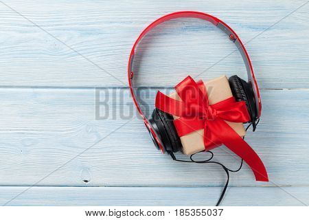 Music gift concept. Headphones and gift box on wooden table. Top view with space for your greetings