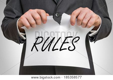 Businessman Tearing Paper With Rules Word
