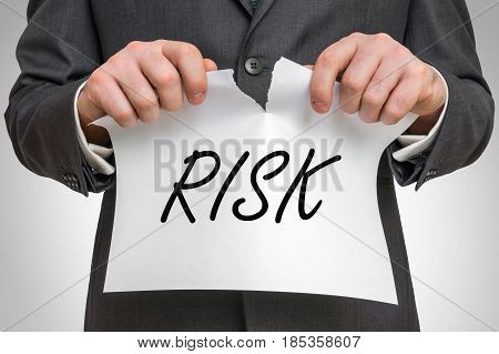 Businessman Tearing Paper With Risk Word