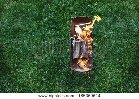 flame grilled and wood burning in fire. family BBQ party in outdoor or home garden. fireplace on the grass.