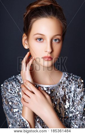 Fashion Portrait. Young Model Wearing Silver Evening Dress. Studio Black Background .
