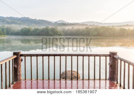 Wooden balcony in front of lake on the morning.
