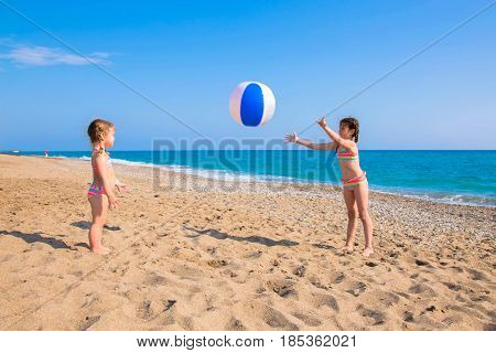 Children playing with beach ball outdoors. Summer vacation family vacation concept.