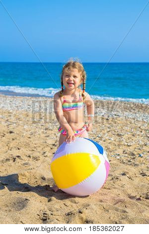Child playing with ball on the beach. Summer vacation family vacation concept.