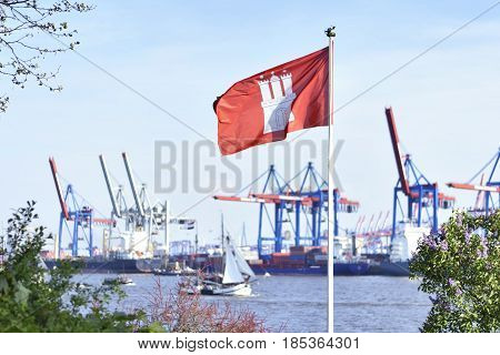 Hamburg harbor, birthday parade with various ships. View to Hamburg harbor with harbor cranes and Hamburg flag in focus.