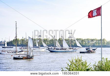Hamburg harbor, birthday parade with various ships. View to a ship parade with Hamburg flag in the foreground.