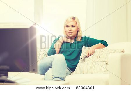 television, leisure and people concept - smiling woman sitting on couch with remote control and watching tv at home