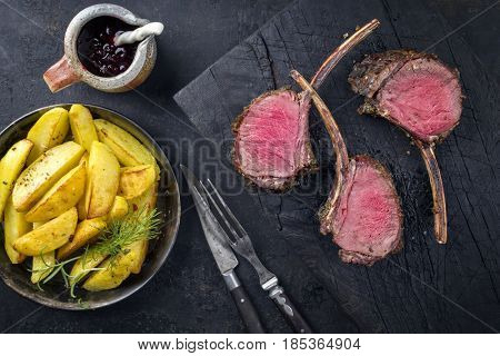 Barbecue Rack of Venison with Potatoes and Cranberries as top view on an old burnt wooden board