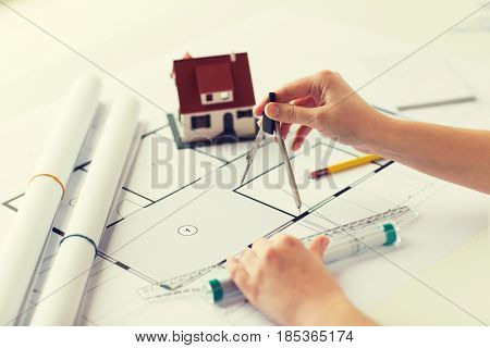 business, architecture, building, construction and people concept - close up of architect hands with compass and ruler measuring living house blueprint