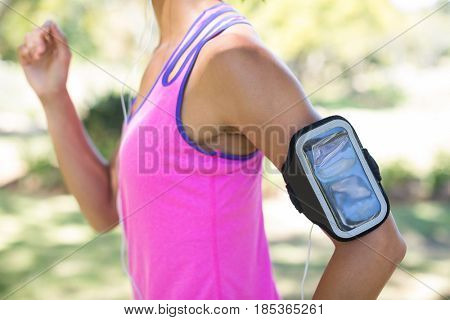 Mid section of female jogger with arm band jogging in the park