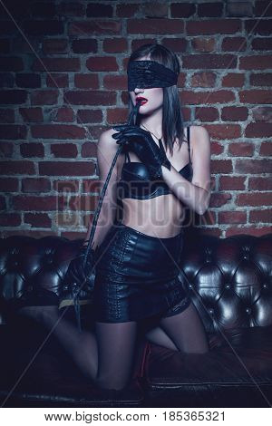 Sexy woman in blindfold and gloves bite whip at night bdsm