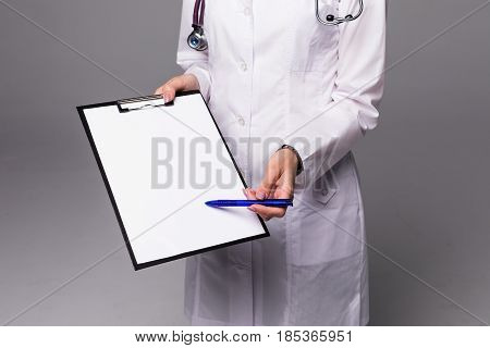 Close Up Nurse Pointing To Clipboard On Grey Background