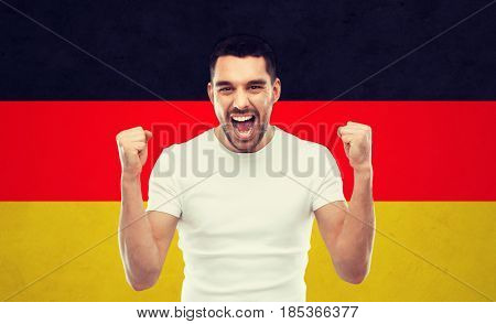 emotion, aggression, gesture and people concept - angry young man or immigrant showing fists over german flag background