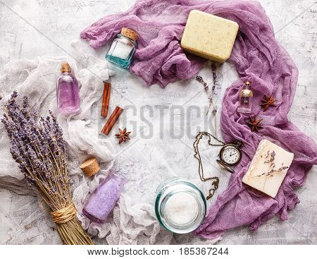 Lavender background with bouquet and twigs of dry lavender bottle with cosmetic oil perfume bottle soap vintage pocket watch cinnamon sticks anise stars and cosmetic salt. Spa and perfume theme. Top view.