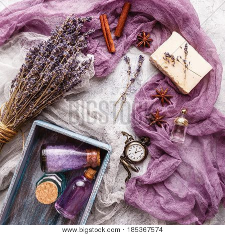 Bottle with aromatic lavender oil and sea salt in a wooden box a bottle of perfume a bouquet of lavender piece of soap and a vintage pocket watch. Top view. Spa and perfume theme