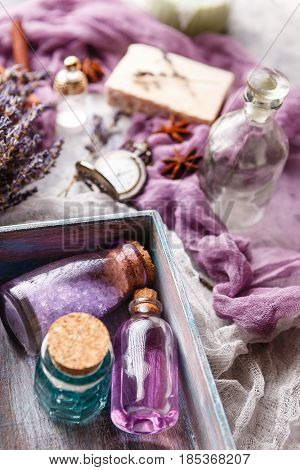 Bottle with aromatic lavender oil and sea salt in a wooden box a bottle of perfume a bouquet of lavender piece of soap and a vintage pocket watch. Selective focus. Spa and perfume theme