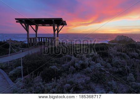 Dramatic clouds at sunset behind a public walkway and gazebo at Asilomar State Beach in Pacific Grove on the Monterey Peninsula of California