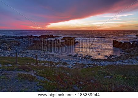 HDR image of dramatic clouds at sunset over the rocks and sand of Asilomar State Beach in Pacific Grove on the Monterey Peninsula of California