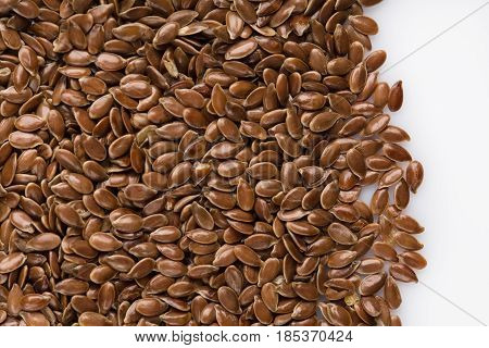 close up of flax seeds isolated on white background. Bowl full of brown flaxseed or linseed. Cereals. Vitamins. Healthy food.